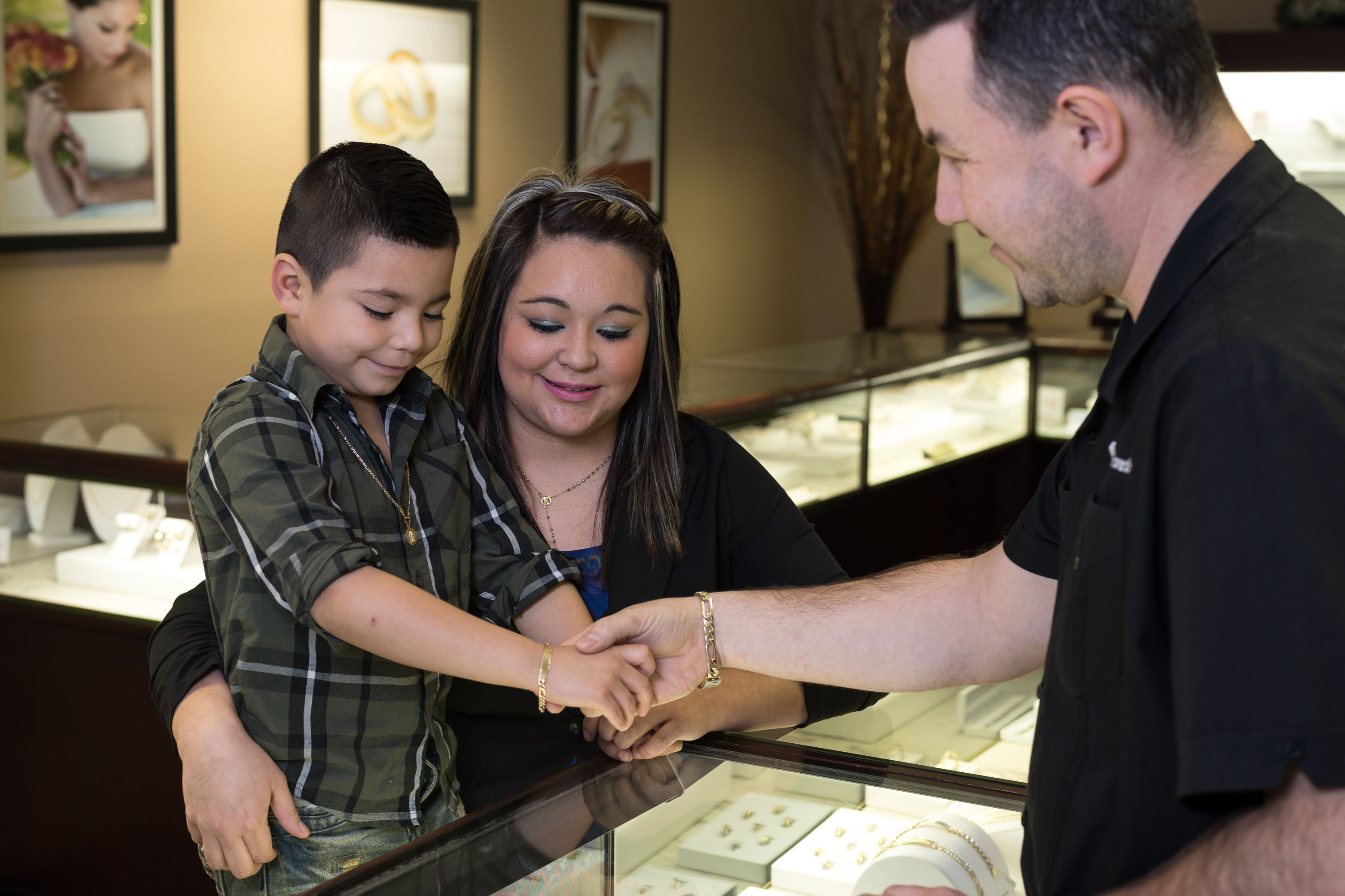 Boy trying on baby & children's jewelry in Kansas City