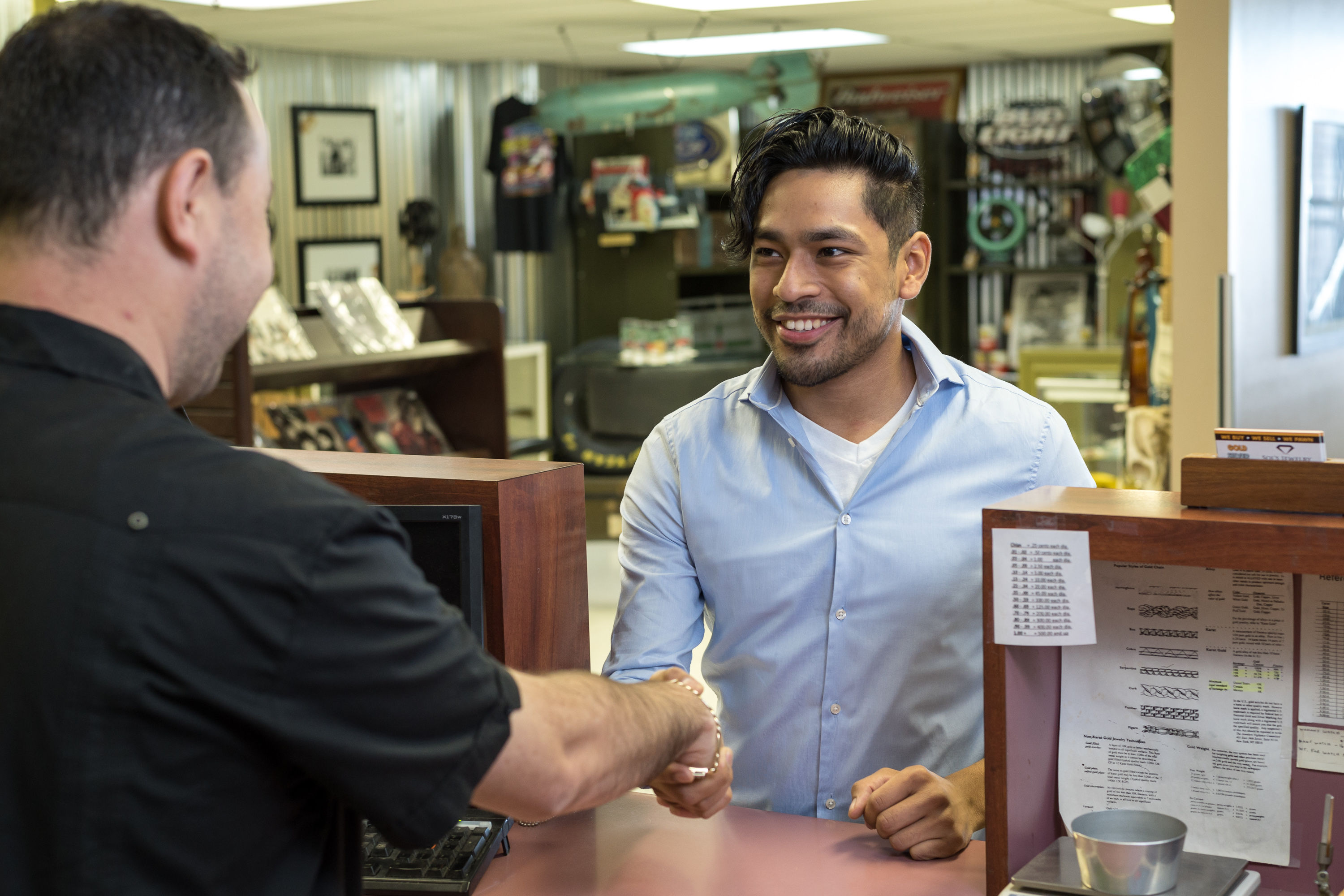 Pawn shop employee shaking hands with a customer